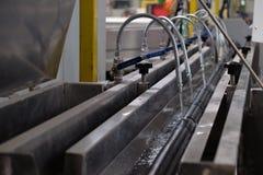 Χάλυβας στροφίγγων και δροσίζοντας νερό για τον καυτό σωλήνα Στοκ Εικόνες