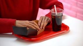 Χάμπουργκερ γυναικείας εκμετάλλευσης με το μη αλκοολούχο ποτό, διατροφή άχρηστου φαγητού, παχύ γεύμα, θερμίδες στοκ εικόνα