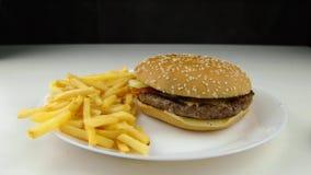 Χάμπουργκερ κάτω στην τηγανισμένη πτώση τσιπ πατατών, σε αργή κίνηση, γρήγορο φαγητό, έννοια άχρηστου φαγητού φιλμ μικρού μήκους