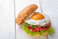 Χάμπουργκερ με τα τηγανισμένα αυγά Στοκ Εικόνα