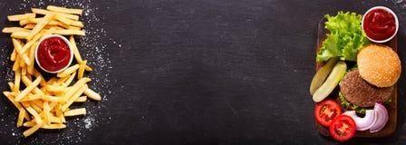 Χάμπουργκερ με τις τηγανιτές πατάτες στο σκοτεινό υπόβαθρο στοκ φωτογραφία με δικαίωμα ελεύθερης χρήσης