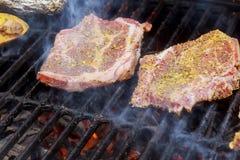 χάμπουργκερ που μαγειρεύουν τα χάμπουργκερ στη σχάρα με τις φλόγες Στοκ Φωτογραφίες