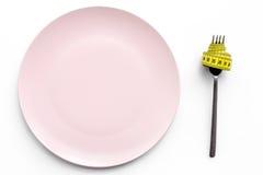 χάνοντας βάρος δίαιτα αυστηρή Κενό πιάτο και μέτρηση της ταινίας στα τρόφιμα δικράνων αντ' αυτού στο άσπρο πρότυπο άποψης υποβάθρ Στοκ Εικόνες