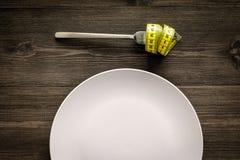 χάνοντας βάρος δίαιτα αυστηρή Κενό πιάτο και μέτρηση της ταινίας στα τρόφιμα δικράνων αντ' αυτού στο ξύλινο πρότυπο άποψης υποβάθ Στοκ Φωτογραφίες