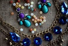 Χάντρα κοσμήματος, αλυσίδες σκουλαρικιών σε ένα καφετί υπόβαθρο σάκων Σχέδιο Στοκ φωτογραφία με δικαίωμα ελεύθερης χρήσης