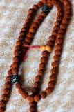 Χάντρες ή rosary Rudraksha πέρα από ένα κλωστοϋφαντουργικό προϊόν στοκ εικόνα