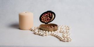 Χάντρες μαργαριταριών, ένα κιβώτιο του ρουζ και άσπρο στρογγυλό κερί Στοκ εικόνα με δικαίωμα ελεύθερης χρήσης