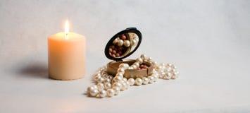 Χάντρες μαργαριταριών, ένα κιβώτιο του ρουζ και άσπρο στρογγυλό καίγοντας κερί Στοκ φωτογραφία με δικαίωμα ελεύθερης χρήσης