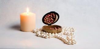 Χάντρες μαργαριταριών, ένα κιβώτιο του ρουζ και άσπρο στρογγυλό καίγοντας κερί Στοκ Εικόνες