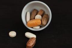 Χάπια βιταμινών σε ένα μαύρο υπόβαθρο Στοκ φωτογραφία με δικαίωμα ελεύθερης χρήσης