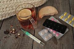 Χάπια, θερμόμετρο, ιατρικό τσάι με το λεμόνι Στοκ Εικόνες