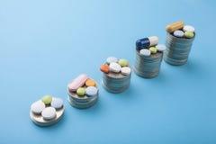 Χάπια ιατρικής και κάψες και νομίσματα σε ένα μπλε υπόβαθρο Στοκ φωτογραφία με δικαίωμα ελεύθερης χρήσης
