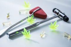 Χάπια κάνναβης CBD μαριχουάνα καννάβεων ως δολοφόνο πόνου ή ιατρική θεραπεία στο γραφείο γιατρών νευρολόγων με το ανακλαστικό σφυ στοκ εικόνες με δικαίωμα ελεύθερης χρήσης