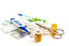 Χάπια και εξοπλισμός πρώτων βοηθειών με το τραπεζογραμμάτιο ως σύμβολο του expe Στοκ Φωτογραφία