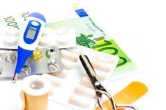 Χάπια και εξοπλισμός πρώτων βοηθειών με το τραπεζογραμμάτιο ως σύμβολο του expe Στοκ Φωτογραφίες