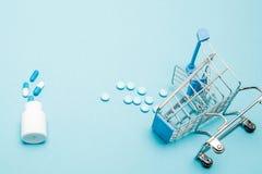 Χάπια και καροτσάκι αγορών στο μπλε υπόβαθρο Δημιουργική ιδέα για το κόστος υγειονομικής περίθαλψης, το φαρμακείο, την ασφάλεια υ στοκ φωτογραφίες με δικαίωμα ελεύθερης χρήσης