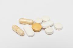Χάπια και σκληρές κάψες στο άσπρο υπόβαθρο Στοκ Φωτογραφία