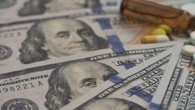 Χάπια και φιαλλίδια που περιστρέφονται στα χρήματα - έννοια δαπανών υγειονομικής περίθαλψης Κινηματογράφηση σε πρώτο πλάνο Η εστί φιλμ μικρού μήκους