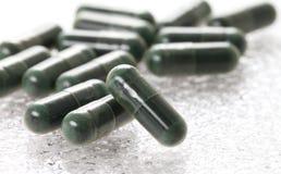 Χάπια καψών στο άσπρο υπόβαθρο, πράσινα χάπια καψών Στοκ Εικόνα