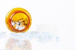 χάπια μπουκαλιών ανασκόπησης που ανατρέπουν το λευκό Στοκ Φωτογραφίες