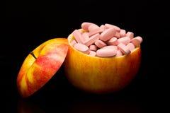 Χάπια σε ένα κόκκινο μήλο Στοκ φωτογραφία με δικαίωμα ελεύθερης χρήσης