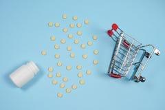 Χάπια στο κάρρο αγορών στο μπλε υπόβαθρο Η έννοια: εμπόριο στα φάρμακα, φαρμακεία στοκ εικόνες
