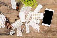 Χάπια, σύριγγα, στηθοσκόπιο και έξυπνο τηλέφωνο στο καφετί ξύλινο γραφείο στοκ εικόνα με δικαίωμα ελεύθερης χρήσης