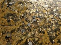 Χάραξη Lotus στο ξάπλωμα της κάλυψης πελμάτων του Βούδα με τα χρυσά φύλλα και το νόμισμα στοκ φωτογραφία
