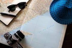 Χάρτης με το καπέλο διασκέδασης και κάμερα σε ένα γραφείο Στοκ Φωτογραφία