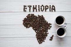 Χάρτης της Αιθιοπίας φιαγμένης από ψημένα φασόλια καφέ που βάζουν στο άσπρο ξύλινο κατασκευασμένο υπόβαθρο με δύο φλυτζάνια καφέ Στοκ Φωτογραφία