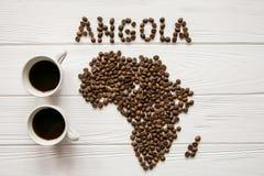 Χάρτης της Ανγκόλα φιαγμένης από ψημένα φασόλια καφέ που βάζουν στο άσπρο ξύλινο κατασκευασμένο υπόβαθρο με δύο φλιτζάνια του καφ Στοκ Φωτογραφία