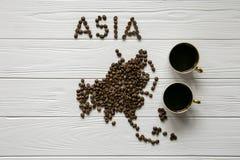 Χάρτης της Ασίας φιαγμένης από ψημένα φασόλια καφέ που βάζουν στο άσπρο ξύλινο κατασκευασμένο υπόβαθρο με δύο φλιτζάνια του καφέ Στοκ φωτογραφία με δικαίωμα ελεύθερης χρήσης