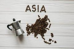 Χάρτης της Ασίας φιαγμένης από ψημένα φασόλια καφέ που βάζουν στο άσπρο ξύλινο κατασκευασμένο υπόβαθρο Στοκ Εικόνες