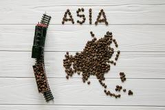 Χάρτης της Ασίας φιαγμένης από ψημένο καφέ beanMap της Ασίας φιαγμένης από ψημένο καφέ bes που βάζει στο άσπρο ξύλινο κατασκευασμ Στοκ Φωτογραφία