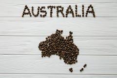 Χάρτης της Αυστραλίας φιαγμένης από ψημένα φασόλια καφέ που βάζουν στο άσπρο ξύλινο κατασκευασμένο υπόβαθρο Στοκ φωτογραφία με δικαίωμα ελεύθερης χρήσης
