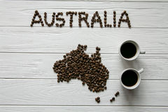 Χάρτης της Αυστραλίας φιαγμένης από ψημένα φασόλια καφέ που βάζουν στο άσπρο ξύλινο κατασκευασμένο υπόβαθρο με δύο φλυτζάνια καφέ Στοκ φωτογραφία με δικαίωμα ελεύθερης χρήσης