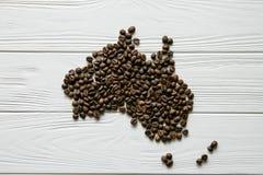 Χάρτης της Αυστραλίας φιαγμένης από ψημένα φασόλια καφέ που βάζουν στο άσπρο ξύλινο κατασκευασμένο υπόβαθρο Στοκ εικόνα με δικαίωμα ελεύθερης χρήσης