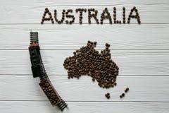 Χάρτης της Αυστραλίας φιαγμένης από ψημένα φασόλια καφέ που βάζουν στο άσπρο ξύλινο κατασκευασμένο υπόβαθρο με το τραίνο παιχνιδι Στοκ Φωτογραφίες