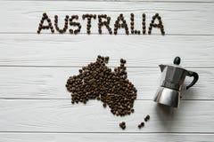 Χάρτης της Αυστραλίας φιαγμένης από ψημένα φασόλια καφέ που βάζουν στο άσπρο ξύλινο κατασκευασμένο υπόβαθρο με τον κατασκευαστή κ Στοκ Εικόνες