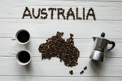 Χάρτης της Αυστραλίας φιαγμένης από ψημένα φασόλια καφέ που βάζουν στο άσπρο ξύλινο κατασκευασμένο υπόβαθρο με κατασκευαστή καφέ  Στοκ Φωτογραφία