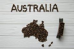 Χάρτης της Αυστραλίας φιαγμένης από ψημένα φασόλια καφέ που βάζουν στο άσπρο ξύλινο κατασκευασμένο υπόβαθρο με το τραίνο παιχνιδι Στοκ φωτογραφία με δικαίωμα ελεύθερης χρήσης