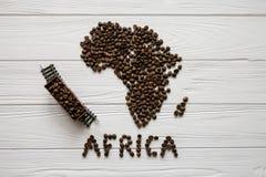 Χάρτης της Αφρικής φιαγμένης από ψημένα φασόλια καφέ που βάζουν στο άσπρο ξύλινο κατασκευασμένο υπόβαθρο με το τραίνο παιχνιδιών Στοκ Εικόνες