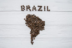 Χάρτης της Βραζιλίας φιαγμένης από ψημένα φασόλια καφέ που βάζουν στο άσπρο ξύλινο κατασκευασμένο υπόβαθρο Στοκ Εικόνες