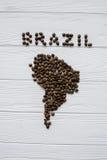 Χάρτης της Βραζιλίας φιαγμένης από ψημένα φασόλια καφέ που βάζουν στο άσπρο ξύλινο κατασκευασμένο υπόβαθρο Στοκ φωτογραφία με δικαίωμα ελεύθερης χρήσης