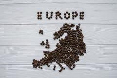 Χάρτης της Ευρώπης φιαγμένης από ψημένα φασόλια καφέ που βάζουν στο άσπρο ξύλινο κατασκευασμένο υπόβαθρο με το φλιτζάνι του καφέ Στοκ φωτογραφία με δικαίωμα ελεύθερης χρήσης