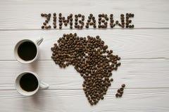 Χάρτης της Ζιμπάμπουε φιαγμένης από ψημένα φασόλια καφέ που βάζουν στο άσπρο ξύλινο κατασκευασμένο υπόβαθρο με δύο φλιτζάνια του  Στοκ φωτογραφία με δικαίωμα ελεύθερης χρήσης