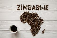 Χάρτης της Ζιμπάμπουε φιαγμένης από ψημένα φασόλια καφέ που βάζουν στο άσπρο ξύλινο κατασκευασμένο υπόβαθρο με το φλιτζάνι του κα Στοκ φωτογραφία με δικαίωμα ελεύθερης χρήσης