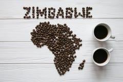 Χάρτης της Ζιμπάμπουε φιαγμένης από ψημένα φασόλια καφέ που βάζουν στο άσπρο ξύλινο κατασκευασμένο υπόβαθρο με δύο φλιτζάνια του  Στοκ Εικόνες