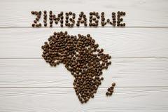 Χάρτης της Ζιμπάμπουε φιαγμένης από ψημένα φασόλια καφέ που βάζουν στο άσπρο ξύλινο κατασκευασμένο υπόβαθρο Στοκ Φωτογραφίες