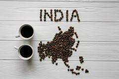 Χάρτης της Ινδίας φιαγμένης από ψημένα φασόλια καφέ που βάζουν στο άσπρο ξύλινο κατασκευασμένο υπόβαθρο με δύο φλιτζάνια του καφέ Στοκ Εικόνες